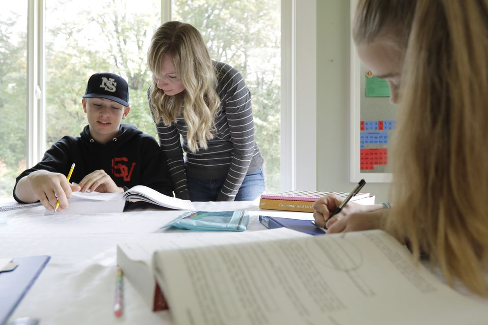 In this Oct. 9, 2019, photo, Donya Grant, center, works on a homeschool lesson with her son Kemper, 14, as her daughter Rowyn, 11, works at right, at their home in Monroe, Wash. The family joined a lawsuit against the Monroe School District and others, alleging that the district failed to adequately respond to PCBs, or polychlorinated biphenyls, at the Sky Valley Education Center, a K-12 public school. Grant has homeschooled her children since they left Sky Valley in 2016 for health reasons that they believe were related to the toxic chemicals. (AP Photo/Ted S. Warren)