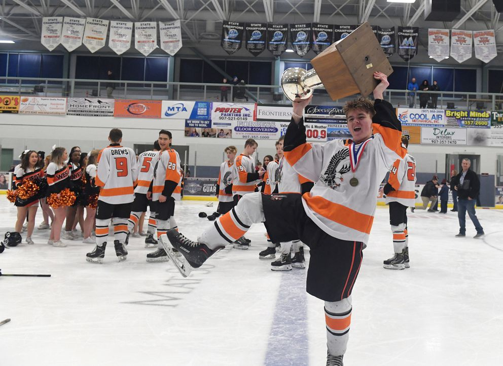 Ian Keim hoists the trophy for West High fans. (Photo by Bob Hallinen)
