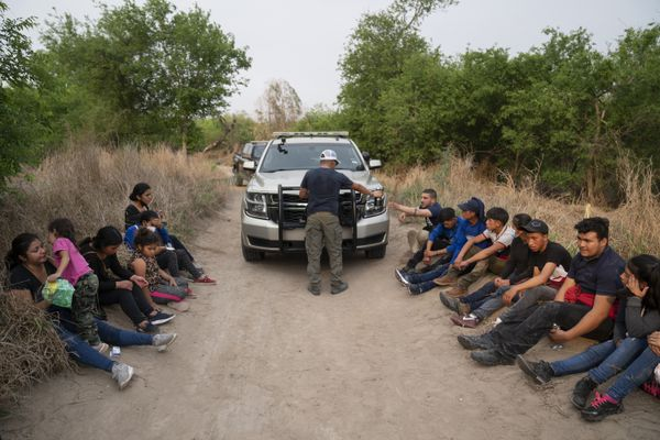 Migrants from Central America, having just crossed the Rio Grande aboard rafts, wait on the side of a dirt road for the Border Patrol on March 24, 2021 in Mission, Texas. MUST CREDIT: Washington Post photo by Michael Robinson Chavez
