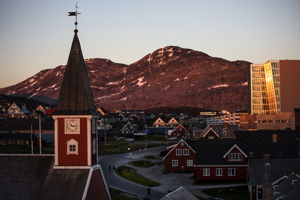 FILE - In this Monday, July. 31, 2017 file photo the sun sets over Nuuk, Greenland. A spokeswoman for Denmark's royal palace says U.S. President Donald Trump's decision to postpone a visit to Denmark next month was