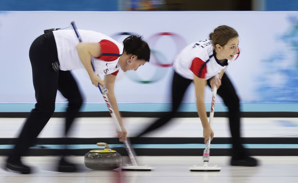 Ann Swisshelm, left, and Jessica Schultz of the United States sweep the ice during the women's curling competition against Russia at the 2014 Winter Olympics, Feb. 11, 2014, in Sochi, Russia. (Wong Maye-E / Associated Press archive 2014)