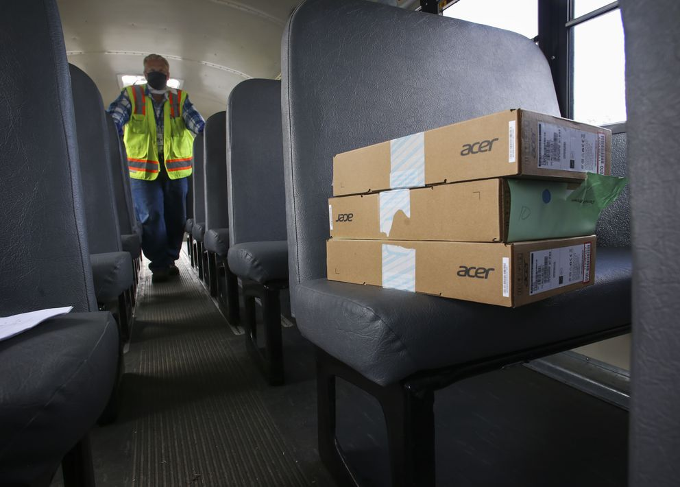 Anchorage School District employee Lloyd Palmatier stands in the back of the school bus as boxes of personal computers rest in a front seat on Aug. 19, 2020. (Emily Mesner / ADN)