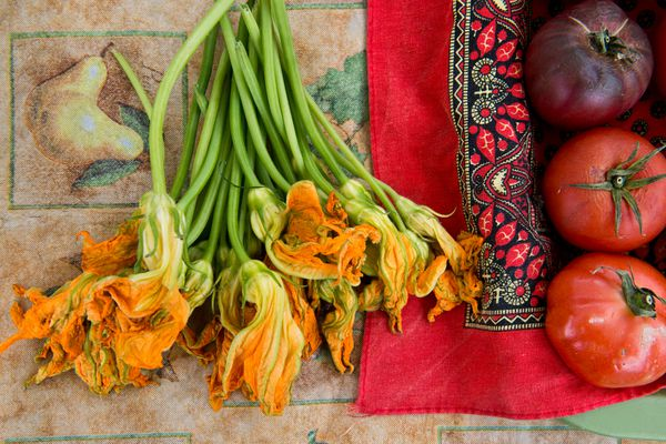 Squash blossoms are for sale at a produce stand run by Soledad Lescas and Manuel Bautista. The Mountain View Farmers Market, in its first year, operates on Thursdays through August along Mountain View Drive. It's hosted by Anchorage Community Land Trust. (Marc Lester / ADN)