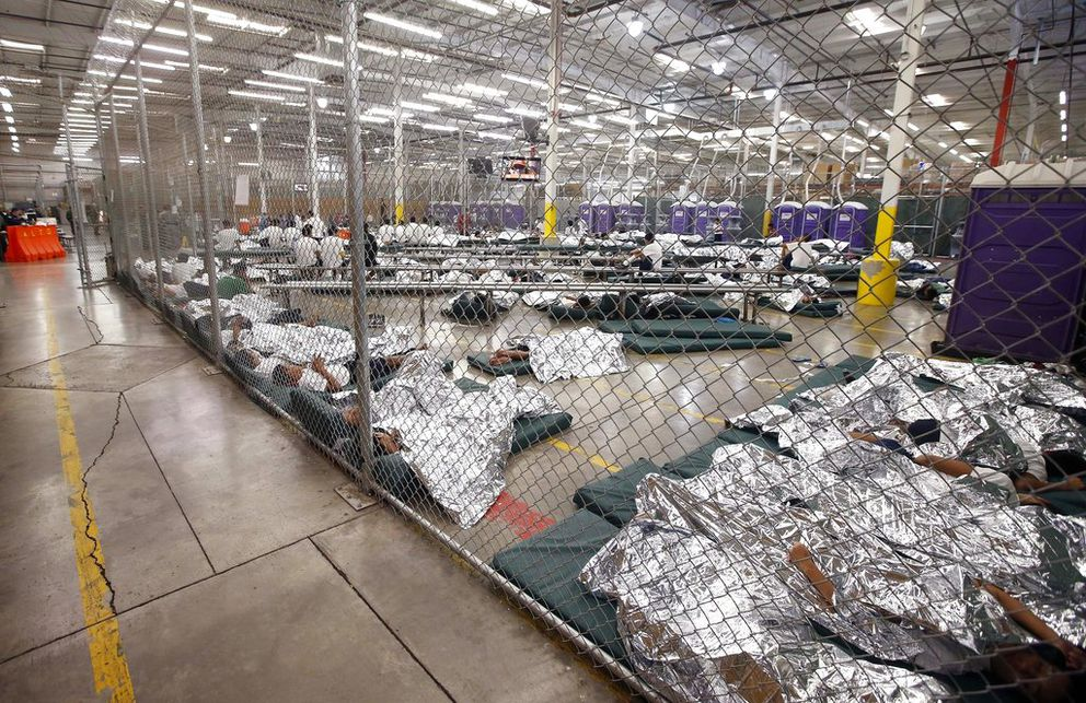In this June 18, 2014, file photo, detainees sleep and watch television in a holding cell where hundreds of mostly Central American immigrant children are being processed and held at the U.S. Customs and Border Protection Nogales Placement Center in Nogales, Ariz. (AP Photo/Ross D. Franklin, Pool)