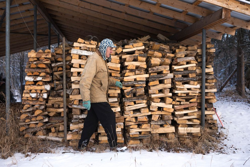 Don Sakis walks past a stack of 13 cords of wood at his Palmer home. (Loren Holmes / ADN)