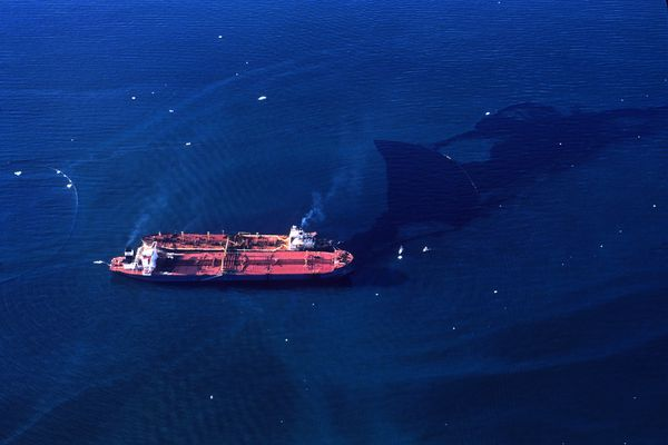 Surrounded by oil containment booms, the smaller Exxon Baton Rouge offloads oil from the grounded Exxon Valdez on Sunday, March 26, 1989, in Prince William Sound. Icebergs dot the water nearby. (Erik Hill / ADN archive 1989)