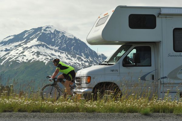 An Alaskaman Extreme Triathlon competitor bikes along the Seward Highway as a motorhome passes by south of Girdwood, Alaska on Saturday, July 15, 2017. (Bob Hallinen / Alaska Dispatch News)