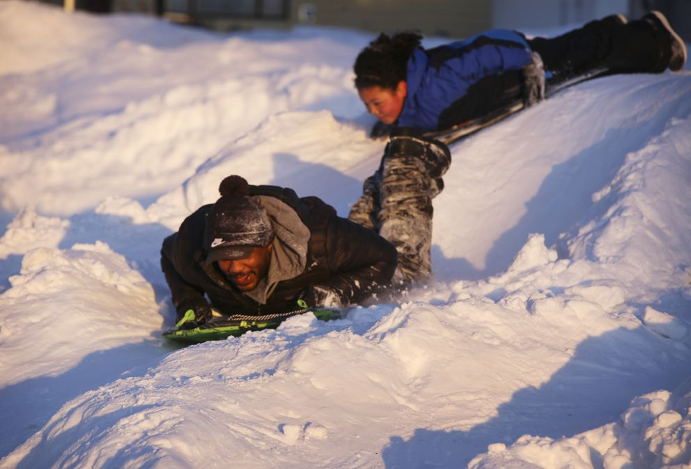Nadia Green sleds with her dad, Keenan Green, on their sledding hill on Friday, March 19, 2021. (Emily Mesner / ADN)