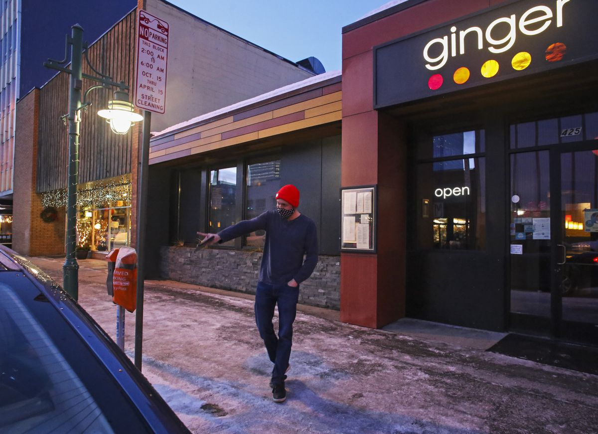 Matt Gill waves goodbye to a customer after walking out their to-go order for curbside pickup at Ginger in downtown Anchorage on Tuesday, Dec. 29, 2020. (Emily Mesner / ADN)