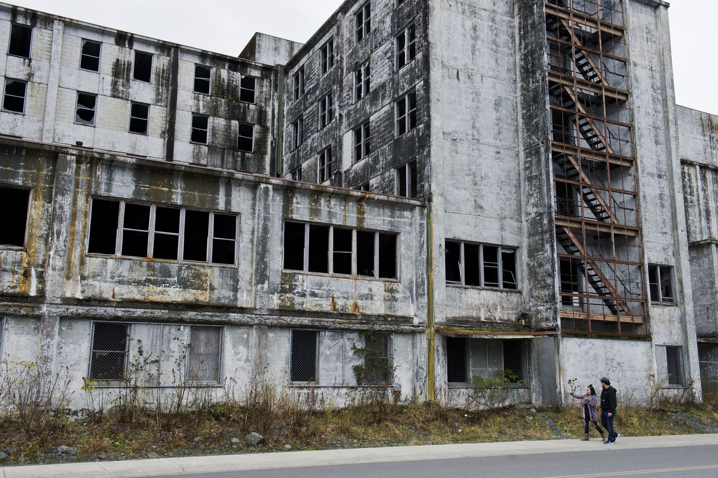 Whittier visitors Breanna Baldwin and Chase Cushingham walk by the Buckner Building in Whittier on Oct. 10, 2017. The abandoned structure once housed hundreds of military personnel in the 1950s. (Marc Lester / Alaska Dispatch News)
