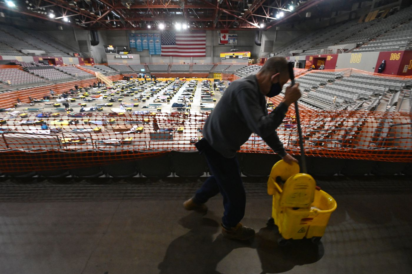 OCTOBER 14. Volunteer Charles Haught mopped around mats used for overflow at the homeless shelter in the Sullivan Arena. (Bill Roth / ADN)
