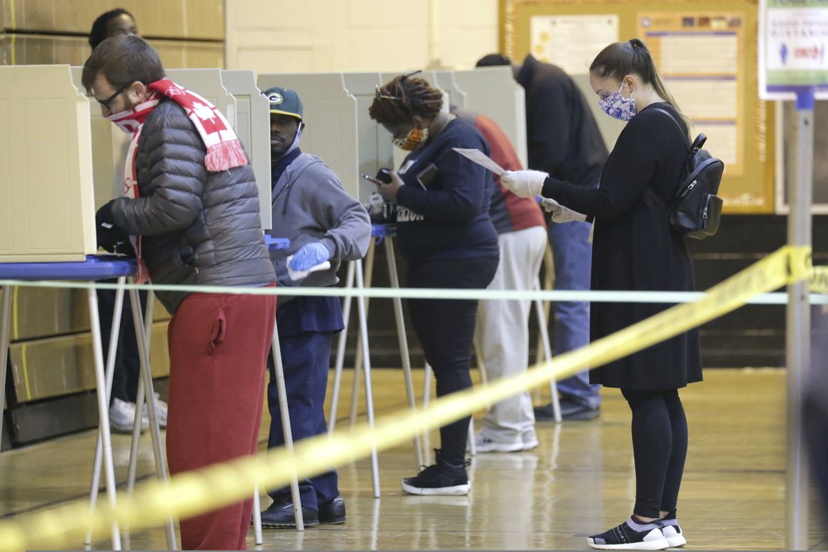 FILE - In this Tuesday April 7, 2020 file photo people vote in Milwaukee, Wis. Alaska Lt. Gov. Kevin Meyer said that Alaska will conduct its August primary election with in-person polling places open. (Mike De Sisti/Milwaukee Journal-Sentinel via AP, File)