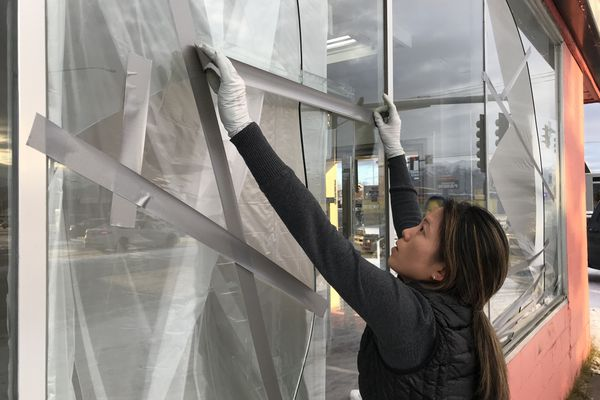 Ami Pyune, owner of Surf Laundry in Mountain View, tapes windows damaged in the earthquake on Friday, Nov. 30, 2018. She said she doesn't have earthquake insurance, as she did in California, and will be paying thousands of dollars to replace the windows. (Bill Roth / ADN)