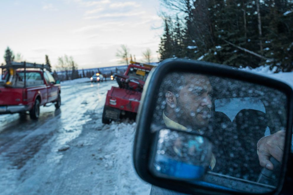 First National Bank employee Hemant Sisodia waits for a second tow truck to extricate him and the tow truck he initially called, which got stuck while trying to help him out of the ditch along Hillside Drive on Thursday morning. (Loren Holmes / Alaska Dispatch News)