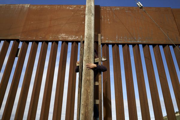 In this Jan. 16, 2019, image, a man uses a ladder to climb an electrical pole in a border neighborhood in Tijuana, Mexico, alongside a newly-replaced section of the border wall. The U.S. faces a delicate dance as it charts a course to extend or replace border barriers near homes and structures. (AP Photo/Gregory Bull)