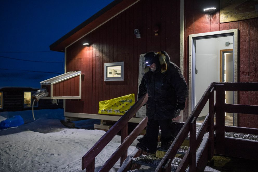 Jim Lanier leaves the washeteria with hot water for his dogs Saturday in Shageluk. (Loren Holmes / ADN)