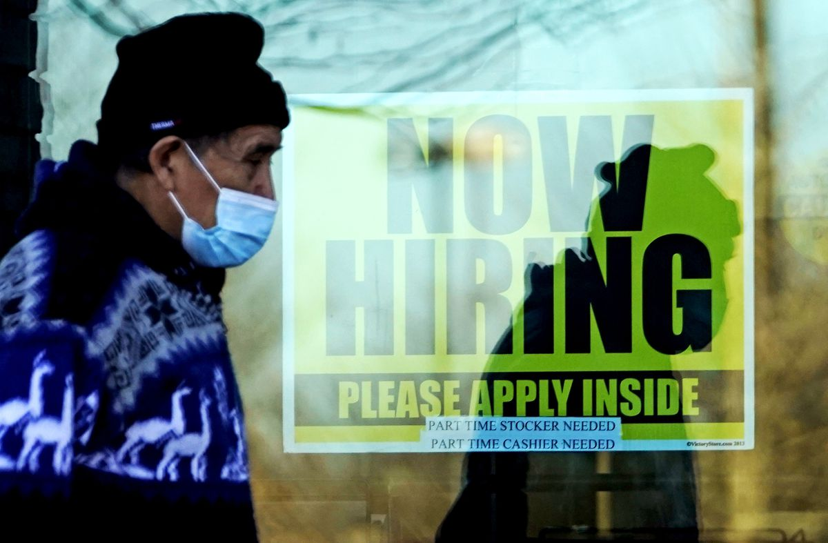 A man walks past a store displaying a hiring sign in Wheeling, Ill., on Nov. 28. (Nam Y. Huh/AP)