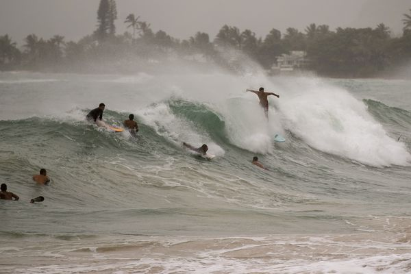 Surfers take on large waves generated by Hurricane Douglas at Laie Beach Park, Sunday, July 26, 2020, in Laie, Hawaii. (AP Photo/Eugene Tanner)