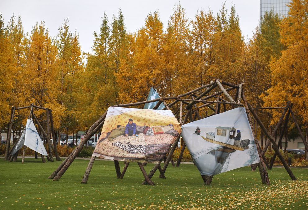 A temporary art installation outside the Anchorage Museum, 'Shelter/Refuge ', features images made by artists working in and depicting Northern landscapes wrapped on structures made by artist Marek Ranis from local timbers, some of which show damage from forest fires, photographed on Sept. 25, 2020. (Emily Mesner / ADN)
