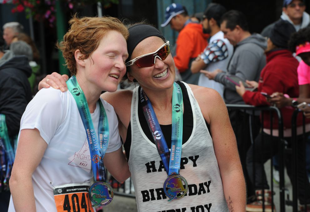 Lia Slemons. left, and Holly Brooks embrace after dueling for second place in the women's marathon. (Bill Roth / ADN)