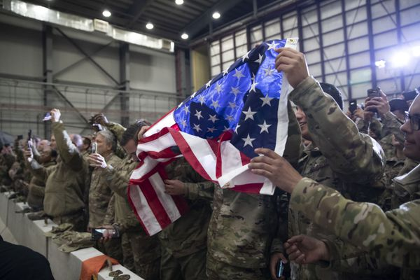 Members of the military unfurl an American flag as President Donald Trump speaks during a surprise Thanksgiving Day visit to the troops, Thursday, Nov. 28, 2019, at Bagram Air Field, Afghanistan. (AP Photo/Alex Brandon)