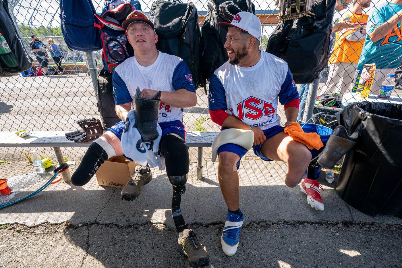 Josh Wege, left, and Saul Monroy adjust their prosthetics during a game. (Loren Holmes / ADN)