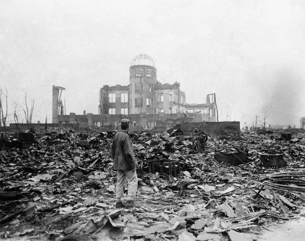FILE - In this Sept. 8, 1945 file photo, an journalist stands on rubble near the shell of a building that once was a movie theater in Hiroshima, Japan, a month after the first atomic bomb ever used in warfare was dropped by the U.S. in World War II. (Stanley Troutman/Pool Photo via AP)