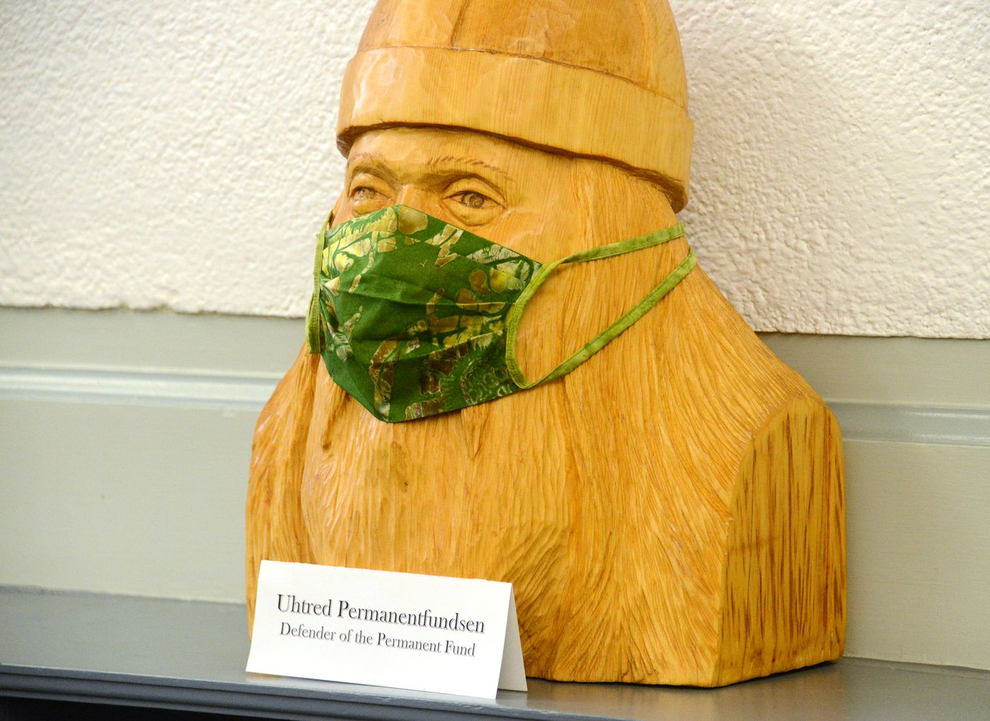 A wooden sculpture of 'Uhtred Permanentfundsen, ' defender of the Alaska Permanent Fund, wears a fabric mask outside the office of Sen. Bert Stedman, R-Sitka, on Monday, Jan. 11, 2021. Stedman represents the town of Petersburg, in Southeast Alaska, which has a rich Scandinavian heritage. (James Brooks / ADN)