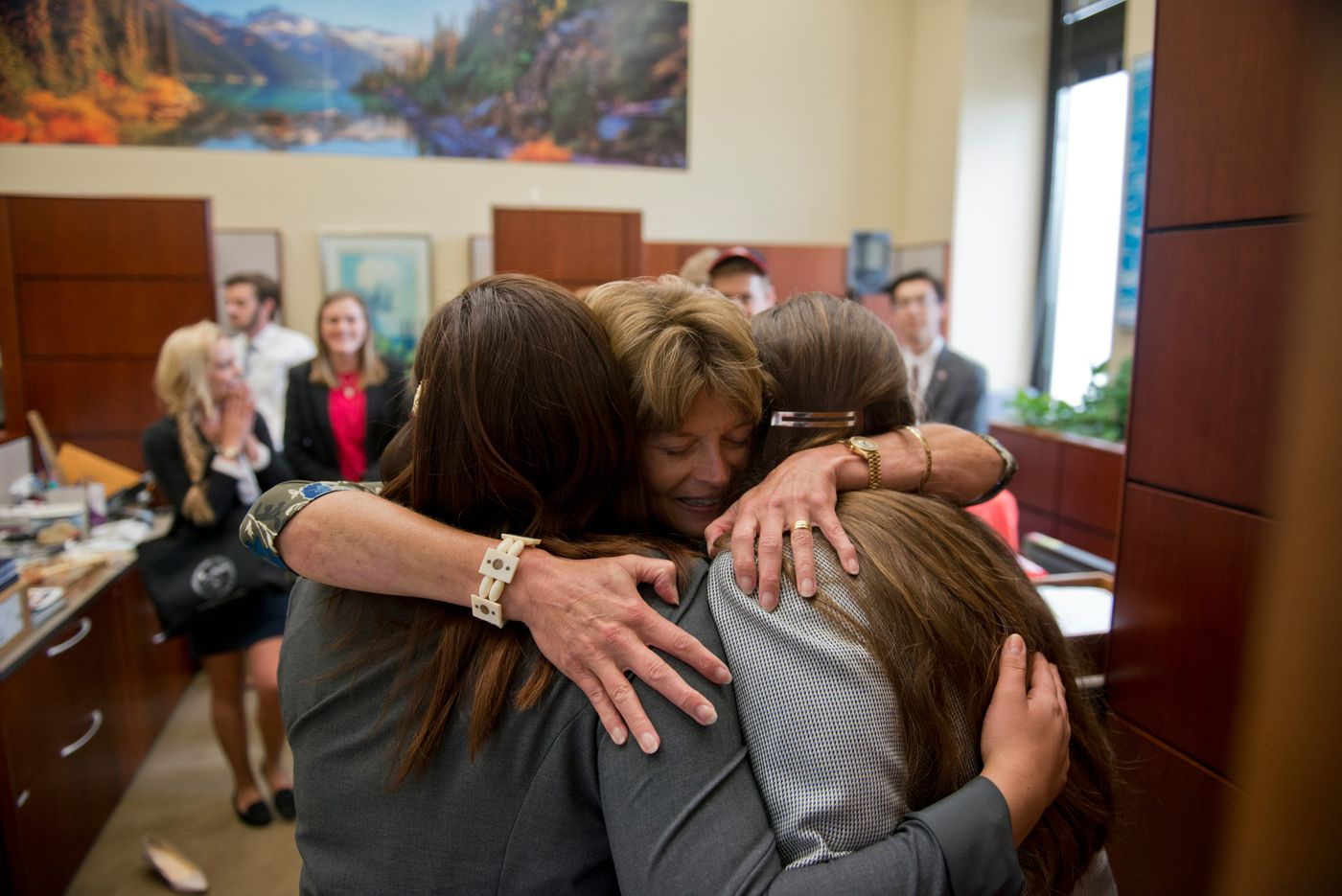 Sen. Lisa Murkowski hugs two interns who sang her the Alaska Flag Song on the last day of their month-long internship in D.C. Denae Benson is at left and Jenna Dreydoppel is at right. (Marc Lester / Alaska Dispatch News )