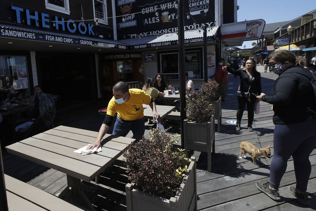 FILE - In this June 18, 2020, file photo a man wears a face mask while cleaning an outdoor dining table at The Hook at Pier 39, where some stores, restaurants and attractions have reopened, during the coronavirus outbreak in San Francisco. (AP Photo/Jeff Chiu, File)