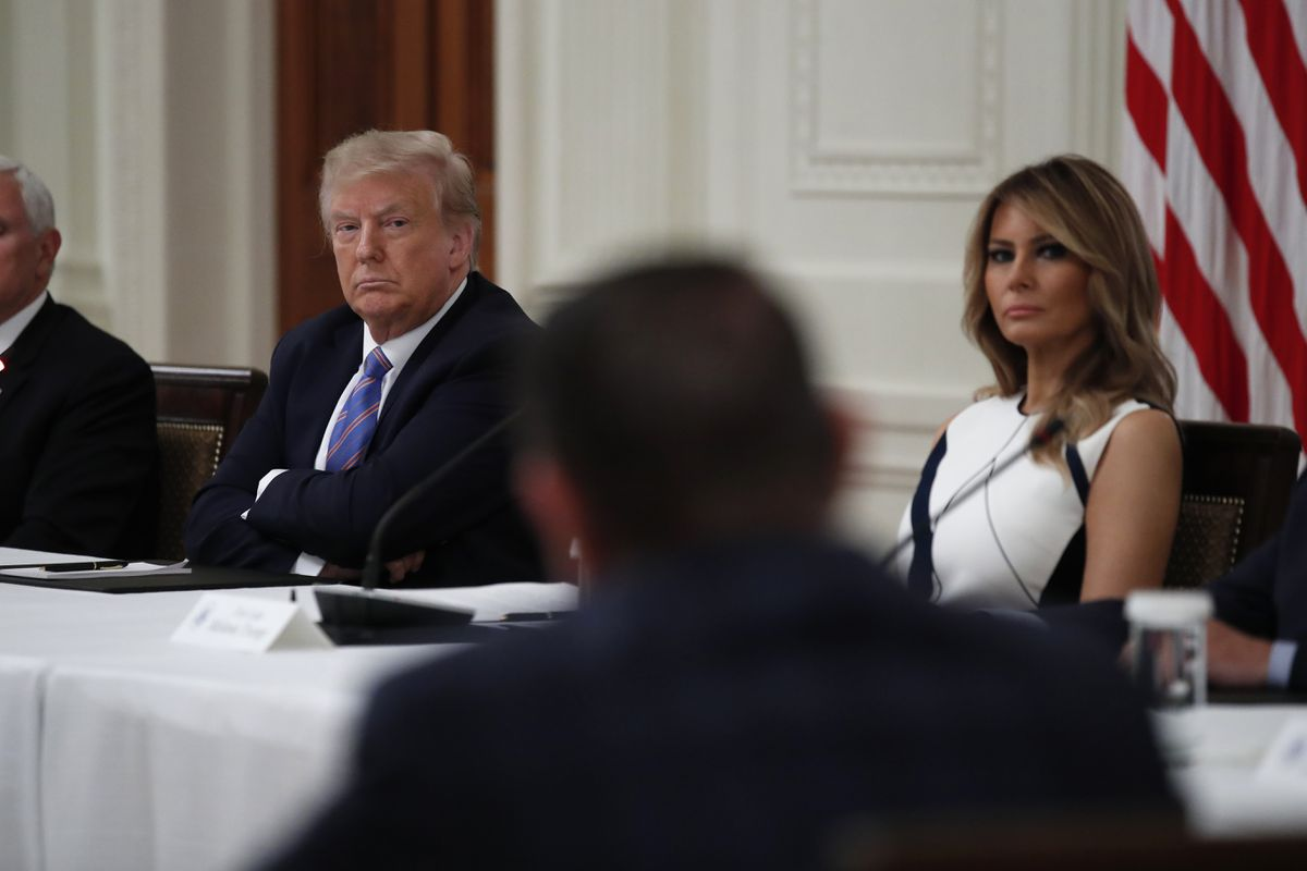 President Donald Trump and first lady Melania Trump listen during a