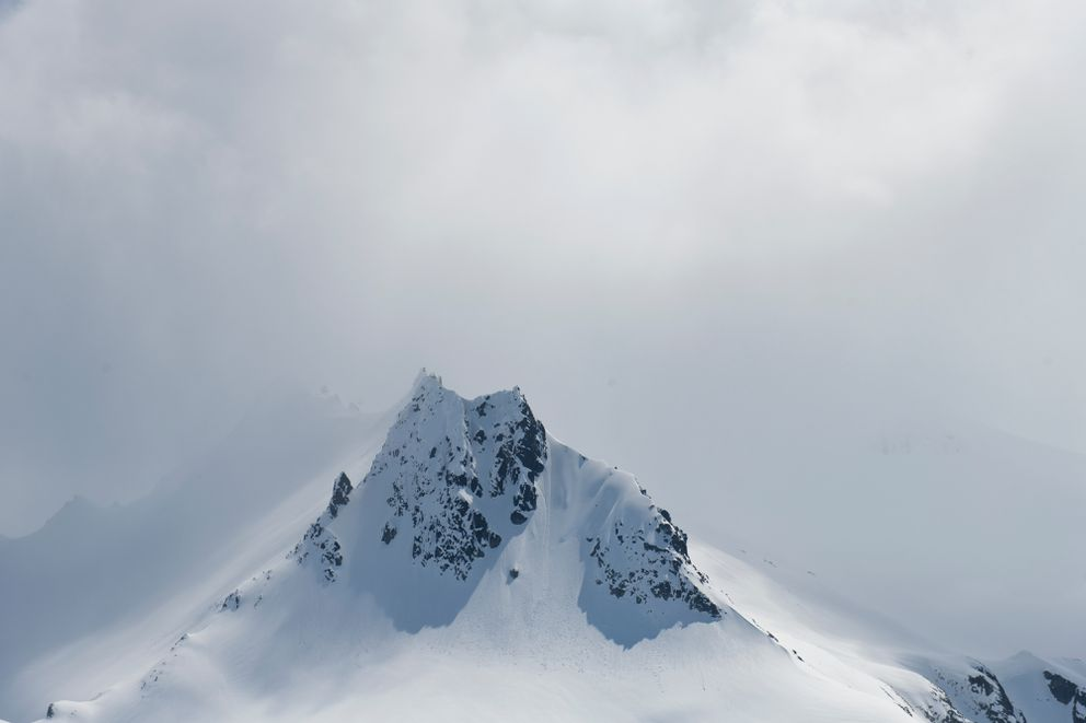 Sharp ridges and peaks of Kodiak Mountain are visible through low clouds during a flight on May 17, 2019. (Marc Lester / ADN)