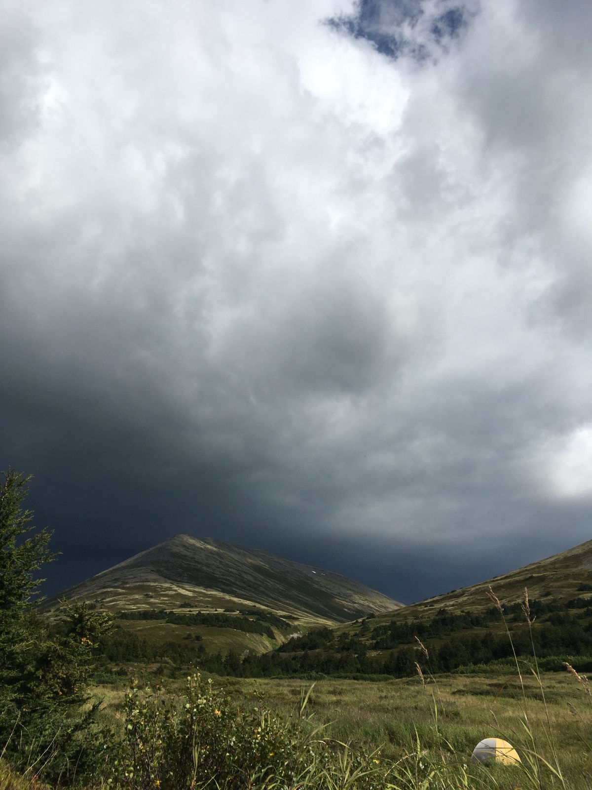 A humble tent sits at a Resurrection Pass campsite as a thunderstorm rolls in. (Photo by Alli Harvey)