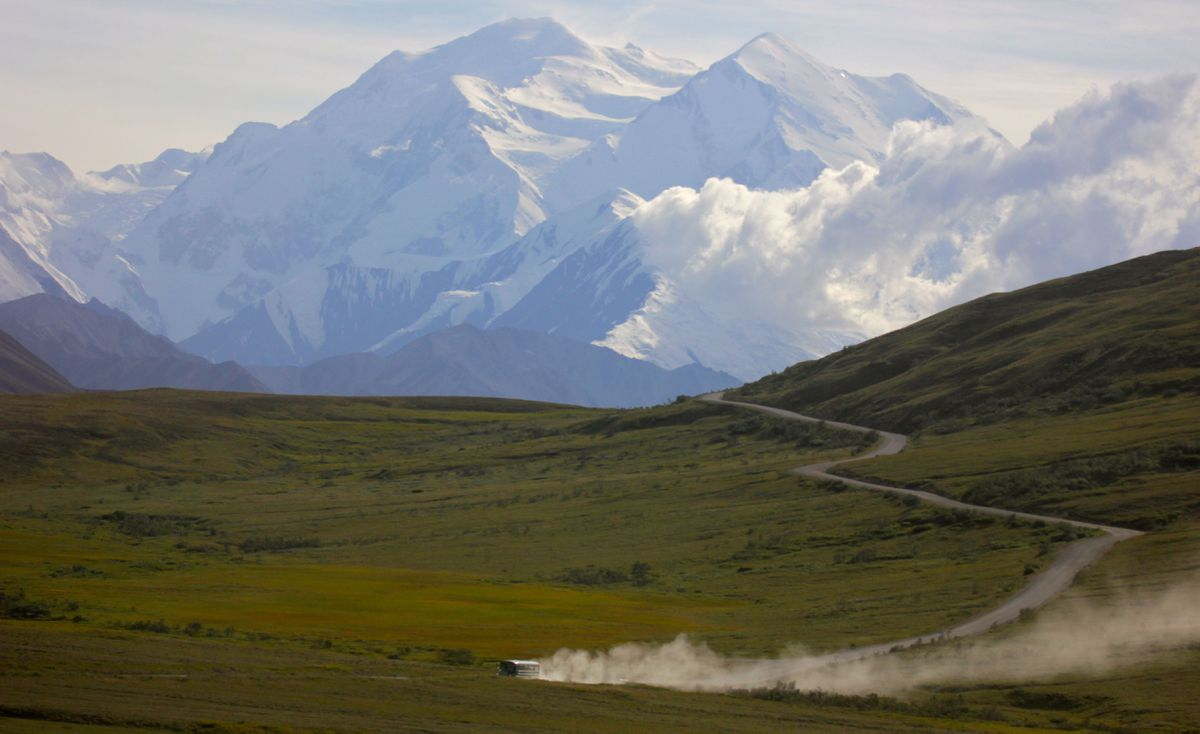 A tour bus kicks up dust during a sunny day at Denali National Park in Alaska as Denali appears in the background in 2013. (AP Photo/Manuel Valdes)
