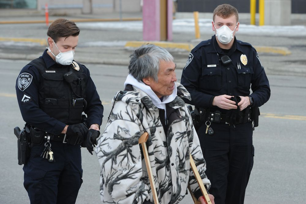 Anchorage Police Officers Johnson and Mayes wore masks while keeping the public away as firefighters battled a structure fire in an abandoned restaurant on Fireweed Lane on Tuesday, April 7, 2020. (Bill Roth / ADN)