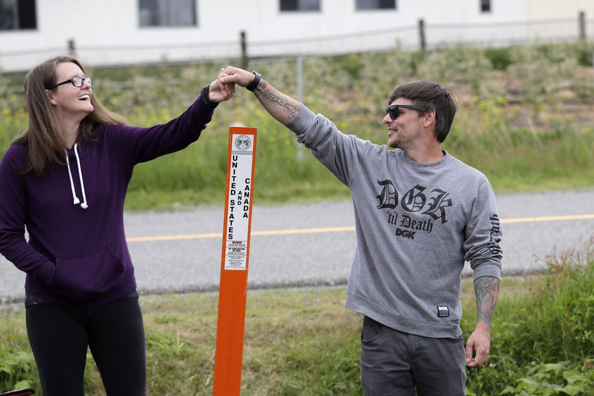 In this photo taken May 17, 2020, Kris Browning, left, stands in Canada and holds hands with her husband, Tim Browning, in the U.S., after posing for a photo at the border near Lynden, Wash. With the border closed to nonessential travel amid the global pandemic, families and couples across the continent have found themselves cut off from loved ones on the other side. (AP Photo/Elaine Thompson)