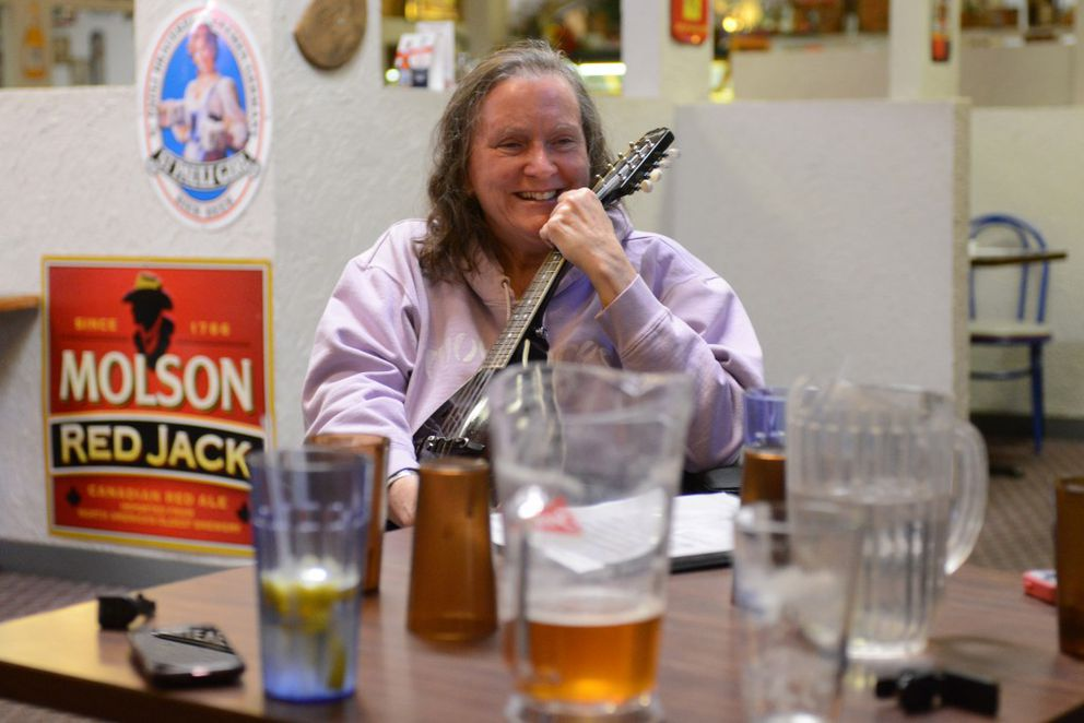 Sherri Hadley shares a laugh with fellow musicians at the weekly Old Time Jam on Thursday at Guido's Pizza. (Erik Hill / Alaska Dispatch News)