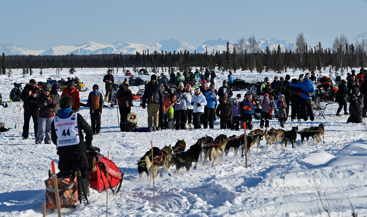 Fans watch musher Jessie Holmes leave the starting area. (Marc Lester / ADN)