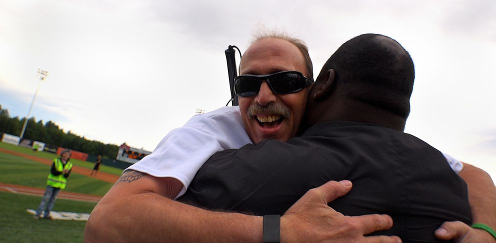 Anchorage Lions Club member Kevin Whitley (left), who is blind, is congratulated by Seattle manager Kevin Daniel after scoring a run for the Seattle Sluggers. (Scott Jensen / Alaska Dispatch News)