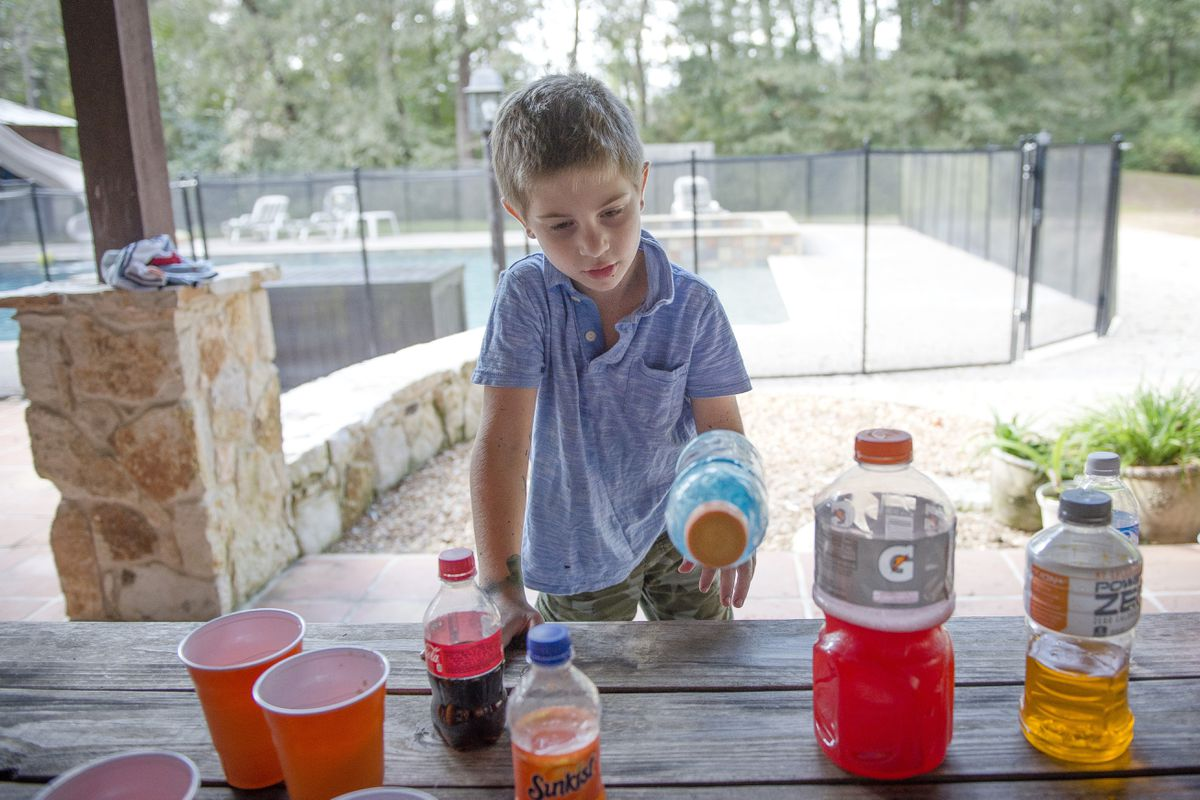 Max Cole, 6, flips bottles in the backyard of his Texas home. On YouTube, trends like bottle-flipping spread quickly among kids of all ages and locations and attract millions of views. (Photo for The Washington Post by Erin Hull)