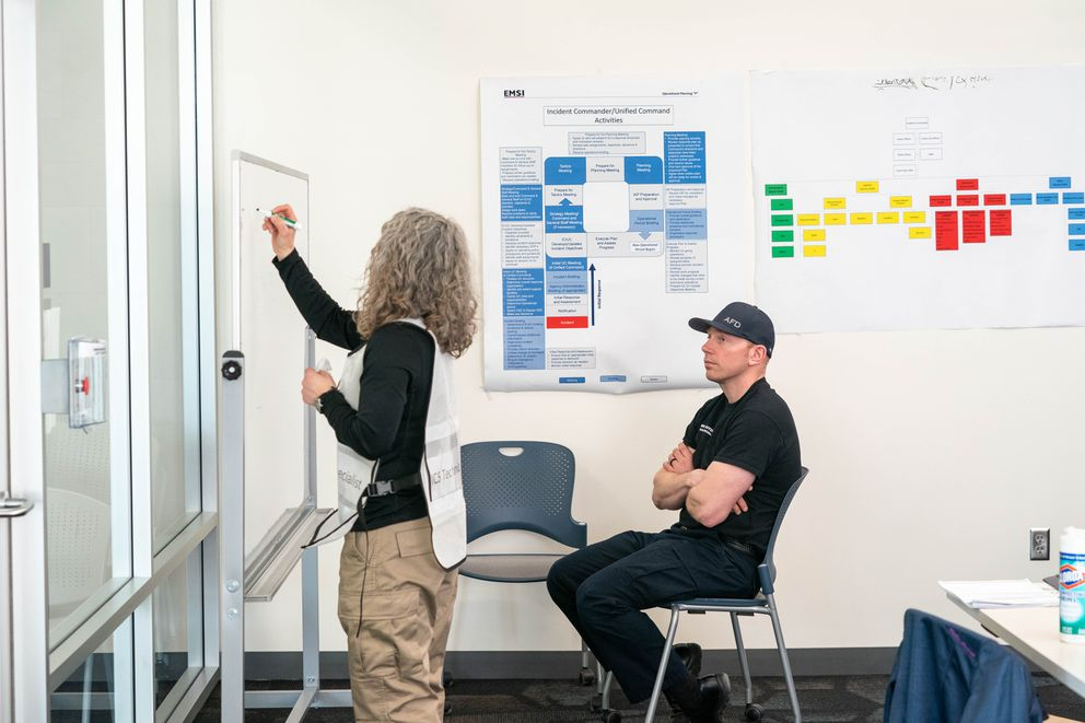 Josh Leutzinger talks with Amy Holman in the incident command room at the new municipal emergency operations center on Thursday, March 26, 2020 at the Loussac Library in Anchorage. (Loren Holmes / ADN)