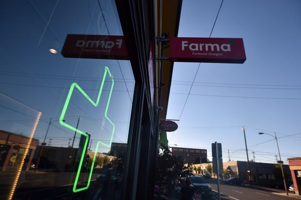 A green cross shines in a window at Farma, a marijuana dispensary in Portland, Oregon, on October 4, 2015. As of October 1, 2015 a limited amount of recreational marijuana became legal for all adults over the age of 21 to purchase in the state of Oregon. (Josh Edelson/AFP/Getty Images/TNS)