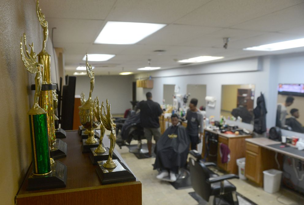 Barber competition trophies mostly won by Marcus Freeman sit on a bookshelf as he cuts Anthony Squalls' hair at Unique Blends on Muldoon Road on Tuesday, Aug. 2, 2016, in Anchorage. (Bob Hallinen / Alaska Dispatch News)