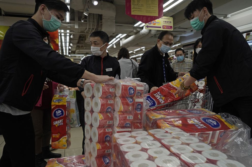 Customers queue to buy supplies of toilet paper in a supermarket in Hong Kong, Friday, Feb. 14, 2020. (AP Photo/Kin Cheung)