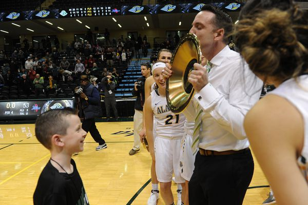 Donovan McCarthy, UAA head coach Ryan McCarthy's son, looks on as his dad kisses his first Shootout gold pan trophy after the Championship game of the 2017 Great Alaska Shootout 59-53 at the Alaska Airlines Center in Anchorage, Alaska on Thursday, Nov. 23, 2017. UAA defeated Tulsa 59-53 to win the women's tournament. (Bob Hallinen / ADN)