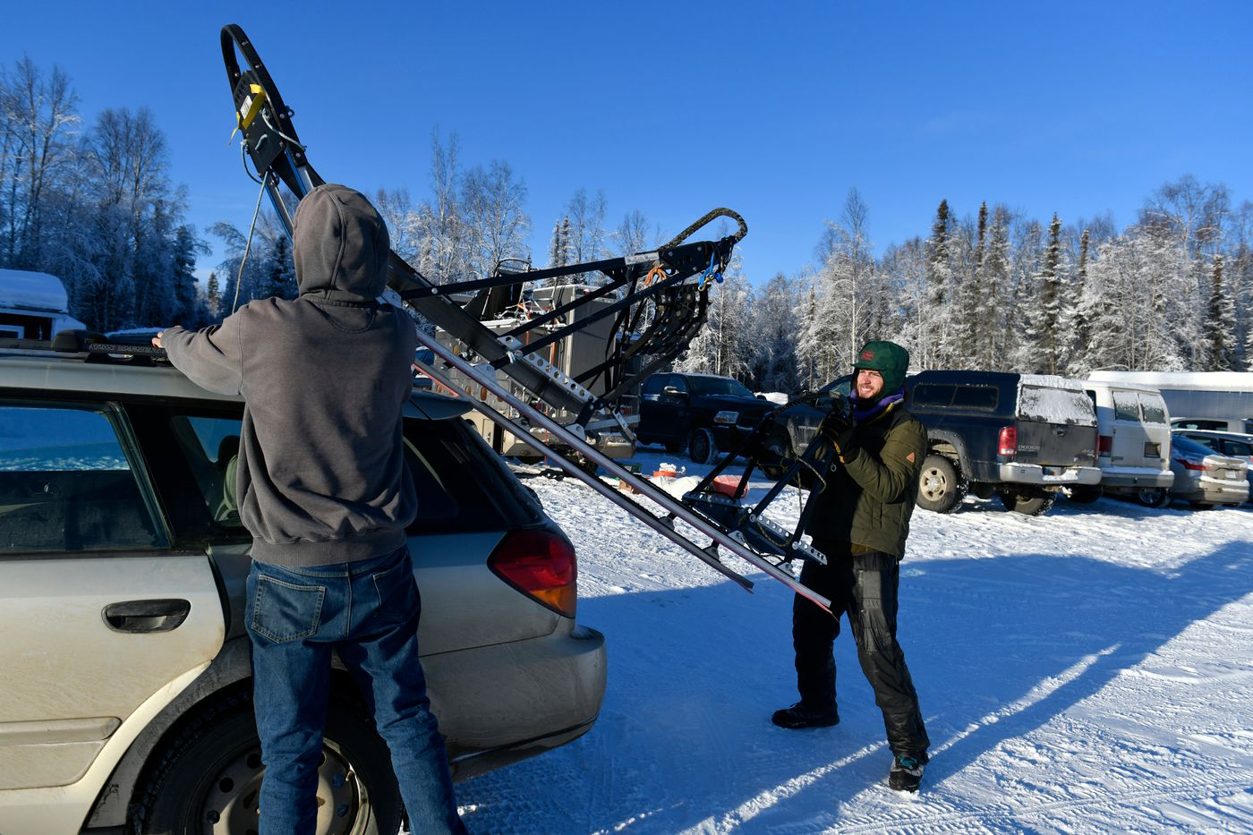 Sean Underwood, right, helps unload a sled he's borrowing to run Iditarod on January 29, 2021, in Talkeetna. (Marc Lester / ADN)