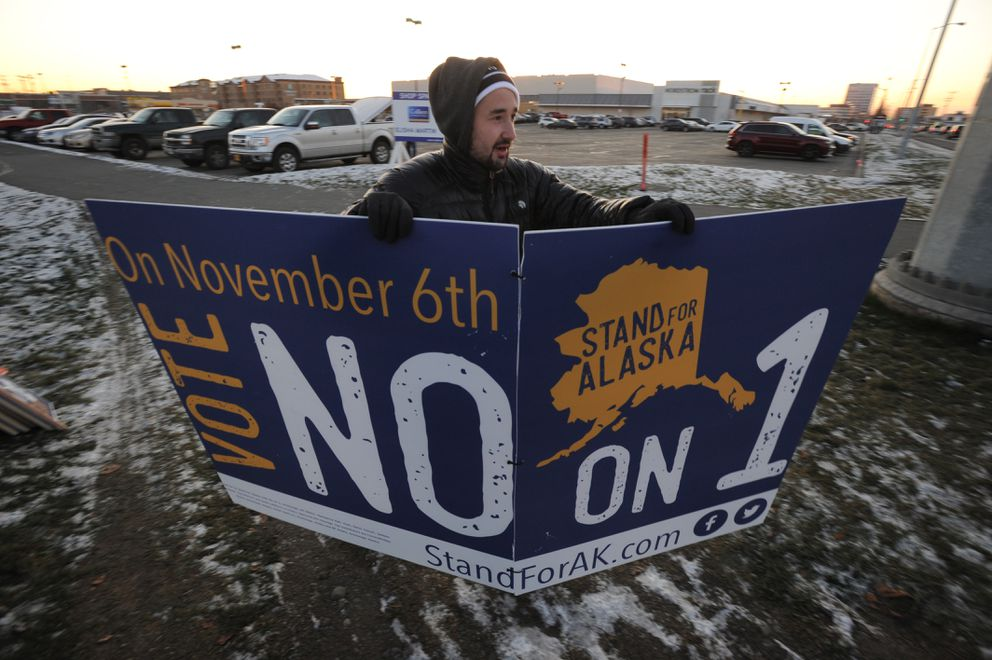Connor Toohey carries a Vote No on 1 sign as people gathered to wave campaign signs at the corner of Northern Lights Boulevard and Seward Highway on Monday, Nov. 5, 2018. (Bill Roth / ADN)