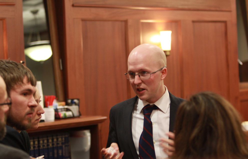 Sitka Democratic Rep. Jonathan Kreiss-Tomkins speaks with legislative aides during a break from House floor debate at the Capitol on Thursday. (Nathaniel Herz / Alaska Dispatch News)