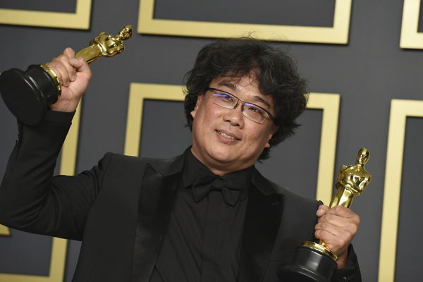 Bong Joon Ho poses in the press room with the awards for best director for