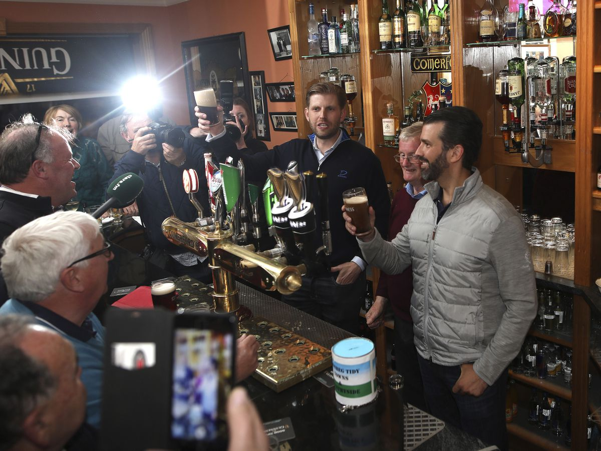 President Trump's sons Eric and Donald Jr., right, pour a pint for locals at a pub in Doonbeg west of Ireland Wednesday, June 5, 2019. President Trump is overnighting in Ireland before attending 75th anniversary of the D-Day landings events in northern France Thursday. (AP Photo/Peter Morrison)
